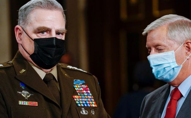 Joint Chiefs Chairman Gen. Mark Milley, left, and Sen. Lindsey Graham, R-S.C., talk as they arrive the chamber ahead of President Joe Biden speaking to a joint session of Congress