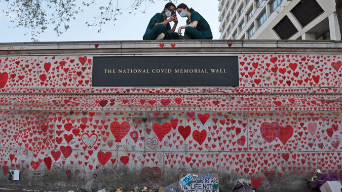 In this Tuesday, April 27, 2021 file photo, nurses from the nearby St. Thomas' hospital sit atop the National Covid Memorial Wall in London. (Photo / AP)