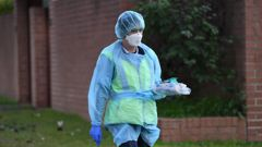 A health worker delivers items to a property at Bondi Junction in Sydney where multiple residents have tested positive for Covid-19 on July 13, 2021. (Photo / Getty Images)
