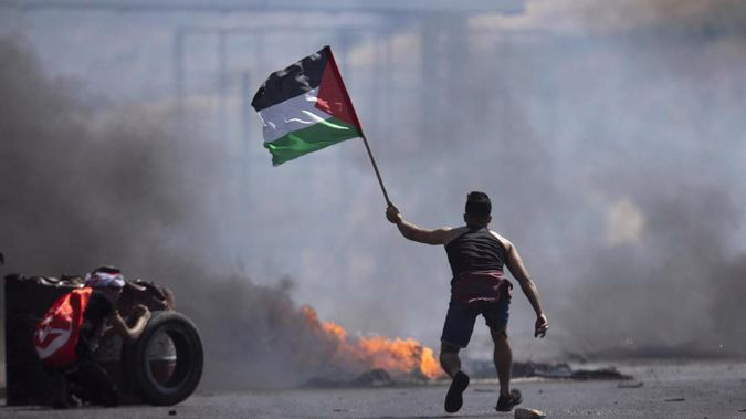 A protester waves the Palestinian flag during clashes with the Israeli forces at the Hawara checkpoint, south of the West Bank city of Nablus. (Photo / AP)