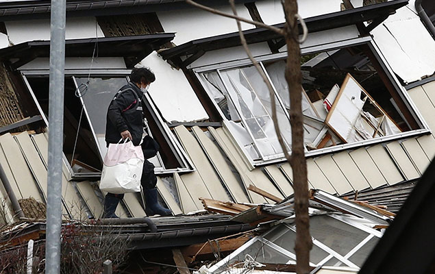 A local resident leaves after picking up her belongings from her collapsed house after a strong earthquake hit the area the night before, in Hakuba, some 300 kms northwest of Tokyo, Nagano prefecture, on November 23, 2014 (Getty)