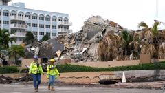 Workers walk past the collapsed and subsequently demolished Champlain Towers South condominium building. (Photo / AP)