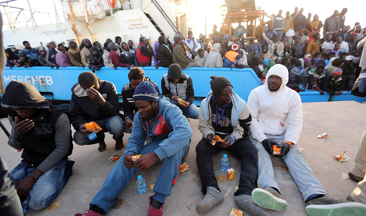 Migrants eat a snack after disembarking from a boat following the interception by the Libyan coastguard of five boats carrying around 500 mostly African migrants trying to reach Europe, on May 3, 2015 (Getty Images)