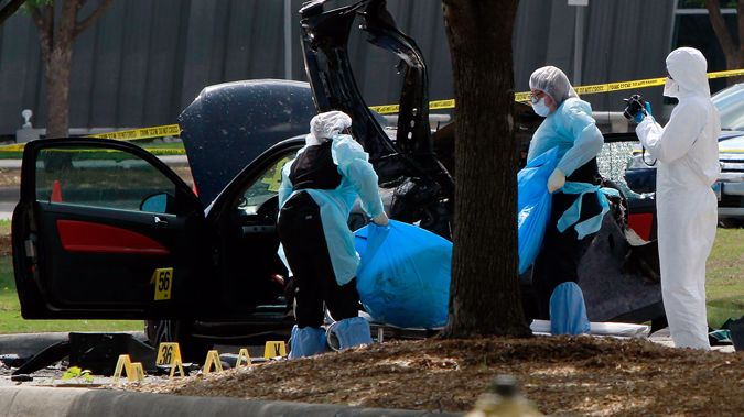 Investigators remove a body as they work a crime scene outside the Curtis Culwell Center (Getty Images)