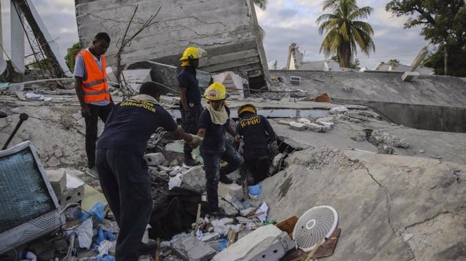 Firefighters search for survivors inside a collapsed building, after Saturday's 7.2 magnitude earthquake. (Photo / AP)