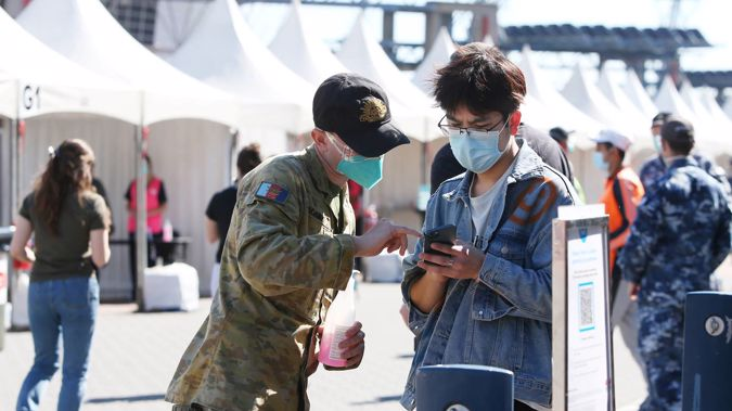 A member of the Australian Defence Force assists people arriving at the Qudos Bank Arena NSW Health Vaccination Centre on August 16, 2021 in Sydney. (Photo / Getty Images)