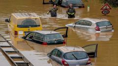 Helpers check for victims in flooded cars on a road in Erftstadt, Germany yesterday. Due to strong rainfall, the small Erft river went over its banks, causing massive damage. Photo / AP