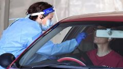 A health worker performs a Covid-19 test at a drive through station in Brisbane. Photo / News Corp Australia