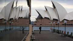 A pedestrian makes their way along Sydney Harbour boardwalk as the list of venues on Covid alert list continues to grow. Photo / Getty Images