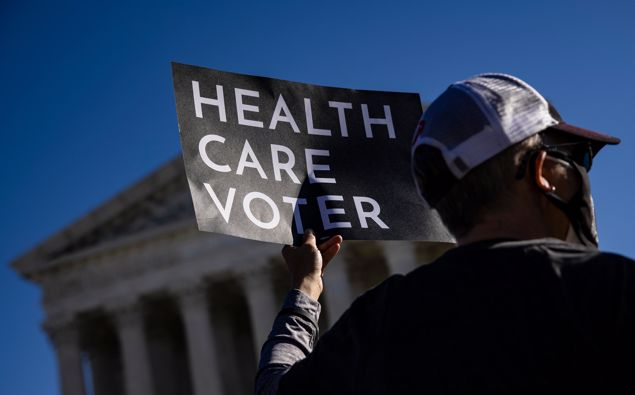 A supporter of the Affordable Care Act (ACA) stands in front of the Supreme Court of the United States in 2020. Photo / Getty Images