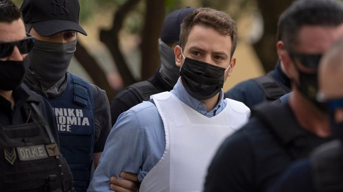 Babis Anagnostopoulos is escorted by police officers as he arrives at a court in Athens on Tuesday. (Photo / AP)