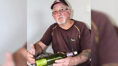 Ken Ferguson with the bottle, complete with a Greek master mariner's card, he found on Ninety Mile Beach. (Photo / Peter Jackson)