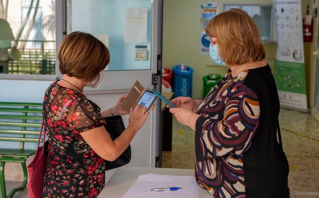 """In this file photo, a teacher has her """"Green Pass"""" checked by a school worker as she arrives at the """"Isacco Newton"""" high school, in Rome. (Photo / AP)"""