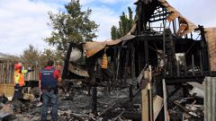 Fire investigator Craig Bain and a detective from Kaikohe police examine the ruins of the Omapere Rd home. (Photo / Peter de Graaf)