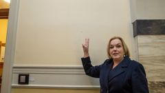 National leader Judith Collins mimics Churchill's V for Victory sign, beside the wall where his portrait once hung. (Photo / Mark Mitchell)