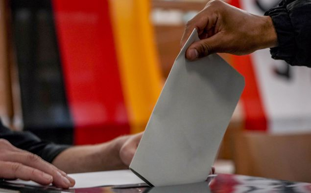 A man casts his ballot for the German elections in a polling station in Berlin, Germany, Sunday, Sept. 26, 2021. In background the German national flag. (Photo / AP)