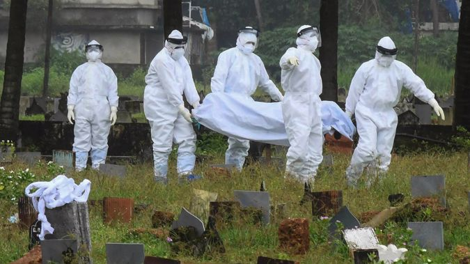 People in protective suits prepare to cremate the body of a 12-year-old boy who died of the Nipah virus in Kozhikode, Kerala, in India. (Photo / AP)