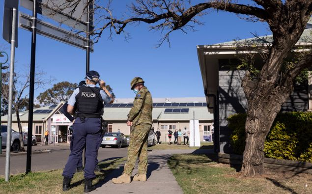 Members of the Australian Defense Force and New South Wales Police are seen outside a pop-up COVID-19 vaccination clinic (Photo/Getty)
