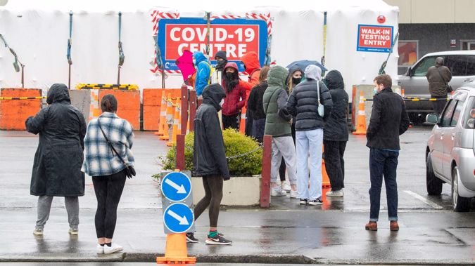 People wearing masks waiting to be tested at the Taranaki St Covid-19 testing station in Wellington. (Photo / Mark Mitchell)