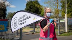 Staff hold signs outside a mobile Covid 19 vaccination centre at Rowandale School, Manurewa. (Photo / Sylvie Whinray)